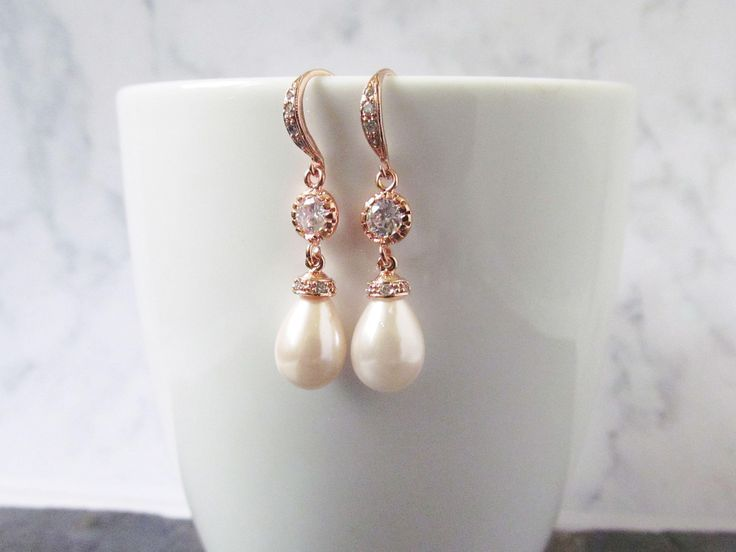 Rose gold pearl bridal earrings with pink pearls, these gorgeous rose gold pink pearl earrings are made with a shell teardrop pearl in a elegant light pink shade and a luxurious cubic zircon ear hook. This earrings is lovely as it is simple and dainty. This mix of luxury and elegance makes it the perfect addition to your wedding or special occasion.