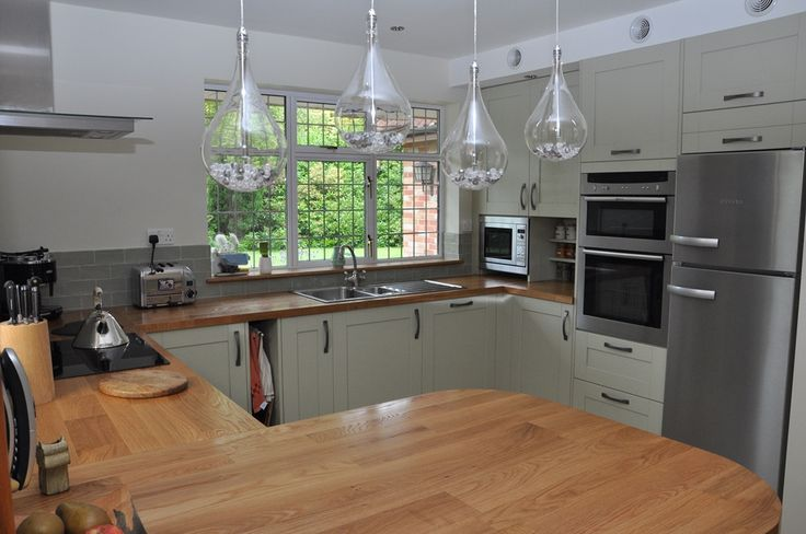 We're obsessed with this Shaker Sage Timber design and its country charm! The oversized, overhanging lightbulbs are a contemporary twist on the traditional kitchen vibe.