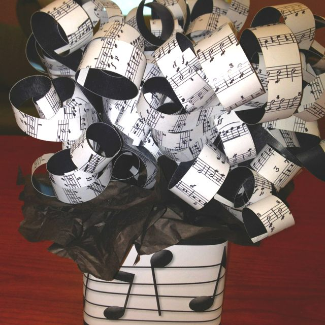 Centerpiece for music themed party. Printed music in paper, cut them in strips and curled them like ribbons. Attached to sticks and stuck them in sand in glass jars. Black tissue paper and printed music on paper wrapped around jar. Cheap and classy.