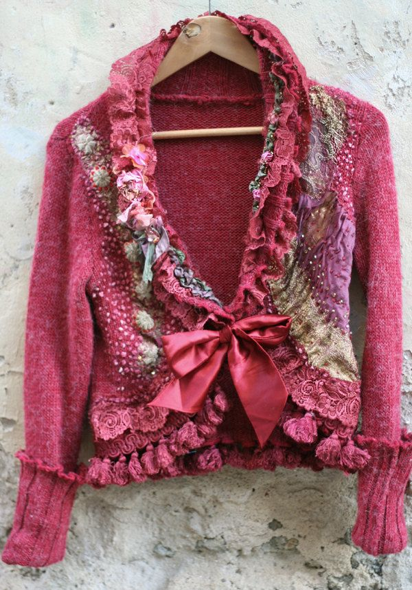 Baroque influenced romantic reworked mohair jacket in shades of reds and faded pinks is lacy and feminine. The ornate frothy collar features scalloped edge lace layers as well sage and pink silk trims and little blooms along beading. The hems are asymmetrically adorned-at one side there is pink and gold woven vintage oriental textile with hand embroidery, at the other mohair stitched pattern and vintage metal embroidered faded silver. The bottom edge is trimmed with scalloped edge ornate…