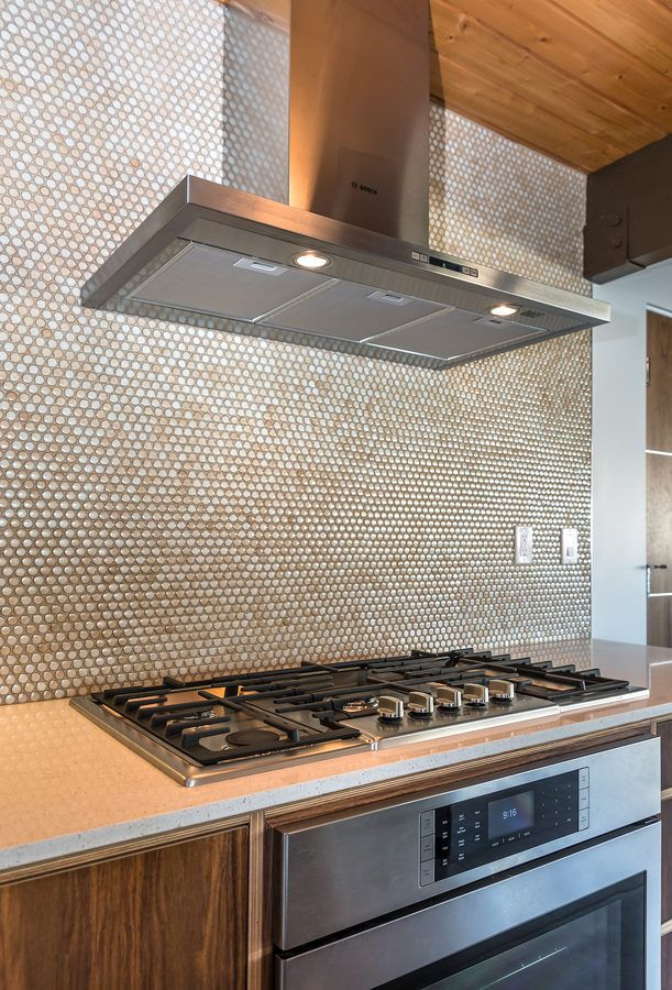 A stainless steel oven, gas stove and sleek range with a circular tile backsplash with wood plank ceiling. Click through for more photos of this Palm Springs home.