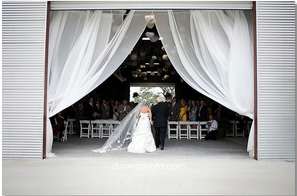 simple white chiffon entry swags to a rustic setting on a barn or fairgrounds goes a long way