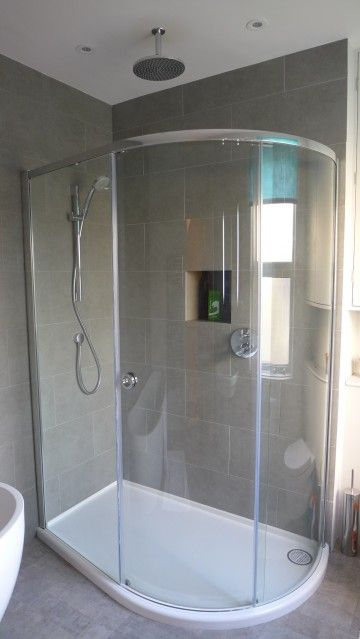 Large offset quadrant shower enclosure with rain shower, handset, large grey porcelain tiles and niche. Vinyl tile floor over electric underfloor heating mat. Just visible freestanding contemporary bath; better images of this on our website.