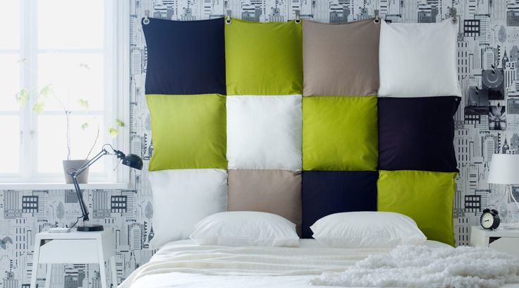 Headboard made of cushions in blue, green, beige and white that has been sewn together- maybe not exactly those colors, but I really really like the idea!