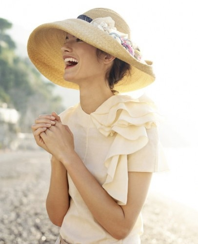 Garbo/Gatsby straw hat with downward swooping brim folded back on itself. Grosgrain band and intricate pale floral decoration. Paired with a cream blush short sleeved blouse, asymmetrically draped and ruffled. The South of France, I think. (Ok, maybe Italy.) Style Planet