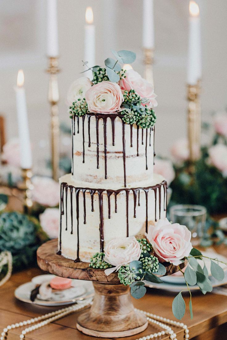 A trendy neaked drip cake made wonderfully elegant for a wedding. Topped with light pink flowers, leaves and greens. This natural wood cake stand is the perfect match to display this cake!