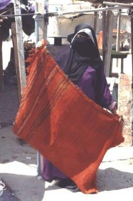 Bedouin woman showing her hand woven merchandise in a souk, Saudi Arabia