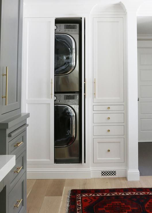 Beautiful laundry room features hidden stacked washer and dryer concealed behind bi-fold cabinet doors across from a gray built-in desk flanked by tall gray built-in cabinets painted Benjamin Moore Chelsea Gray adorned with long brass pulls.