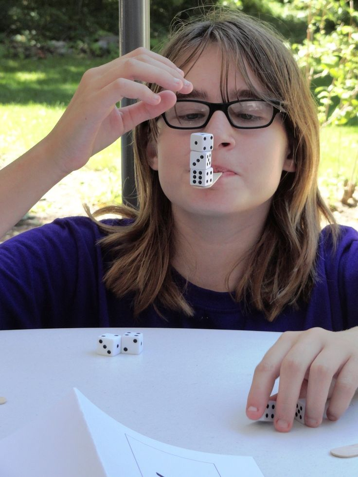 """In the game """"Dicey,"""" teens raced to vertically balance as many dice as they could on Popsicle sticks held in their mouths. They had one """"minute to win it."""""""
