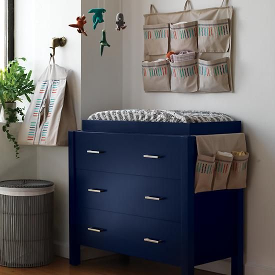 The Land of Nod's Uptown 3-Drawer Changing Table features clean, crisp lines for a modern look in four easy-to-coordinate finishes. Drawers feature smooth metal undermount glides and zinc drawer pulls with a matte silver finish. Choose from painted White, Grey, Midnight Blue or stained Brown.