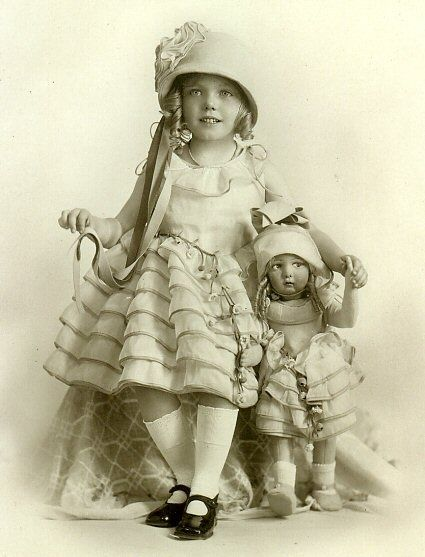 Antique photo of a beautiful little girl with her Lenci doll, outfits appear to match, circa 1900.