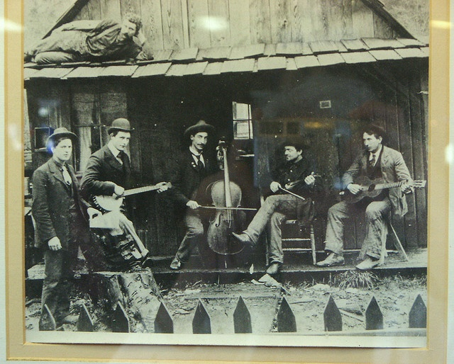 1890s country band, banjo, cello & guitars - porch of small wood shack - Vintage Photo hanging at the One Log House Souvenir Store by DominusVobiscum, via Flickr