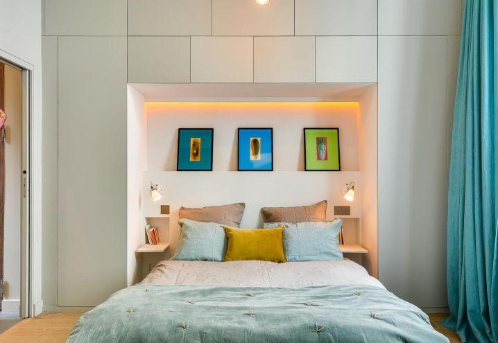 Atmosfera quieta nella zona notte, composta da un letto a una piazza e mezza incastonato in una parete con scaffali e vani per lo storage in total white. La progettista Tatiana Nicol ha scelto stampe e tessuti colorati, in contrasto con la palette cromatica chiara