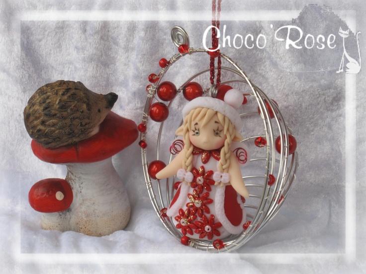 C'est une petite fée de Noël réalisée en modelage de de pâte FIMO, blottie dans une demi-sphère de fil métallique torsadé orné de perles et de grosses rocailles. La boule mesure environ 9cm de diamètre. Du rouge, de l'argenté et quelques paillettes, tout est prêt en attendant la venue du Père-Noël !