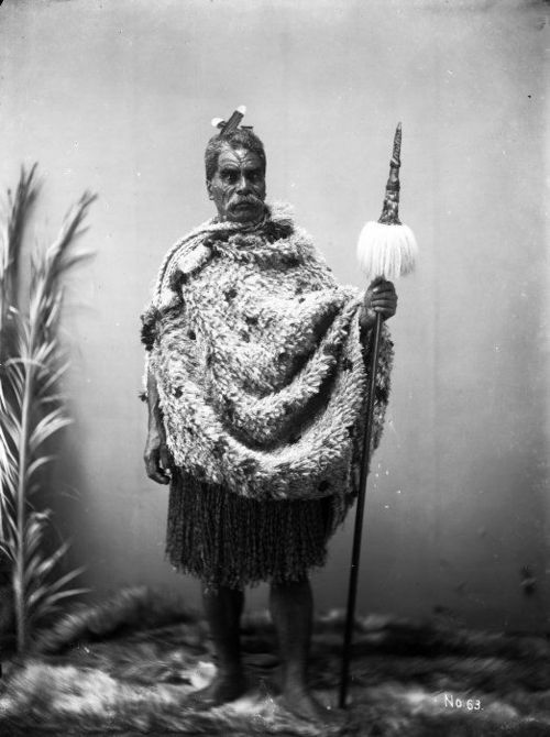 Unidentified Maori man wearing traditional clothing, between 1875-1910  Studio  portrait of an unidentified Maori man wearing traditional clothing. He  wears a kakahu (cloak) and holds a taiaha (traditional Maori fighting  staff). Photograph taken by William Andrews Collis in New Plymouth,  between 1875 and 1910.