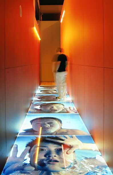 The exhibition divides the works of art into four overriding themes: People and Place, Performing the Self, Re-imagining the Body, and History and Memory. Still photographs, video and projections were displayed alongside one another, breaking away from the usual separation of media. The layout of the exhibition evoked the energy and claustrophobia of the Chinese metropolis, with glimpses of bright neon and projections through apertures in the structure.