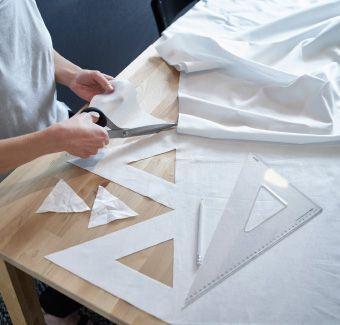 Begynd med at flytte din sofa og dit sofabord.  Du kan bruge borde og stole fra resten af hjemmet. Det gør ikke noget, hvis de ikke matcher. Du dækker bare bordene med en dug eller metervarer.   Og du kan gøre en hvid dug mere smart med lidt gør-det-selv. Du klipper bare et mønster i kanten af stoffet. Du behøver ikke at sy!