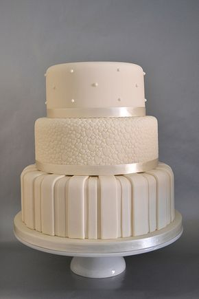 Three tiered different patterns and textured ivory and satin wedding cake