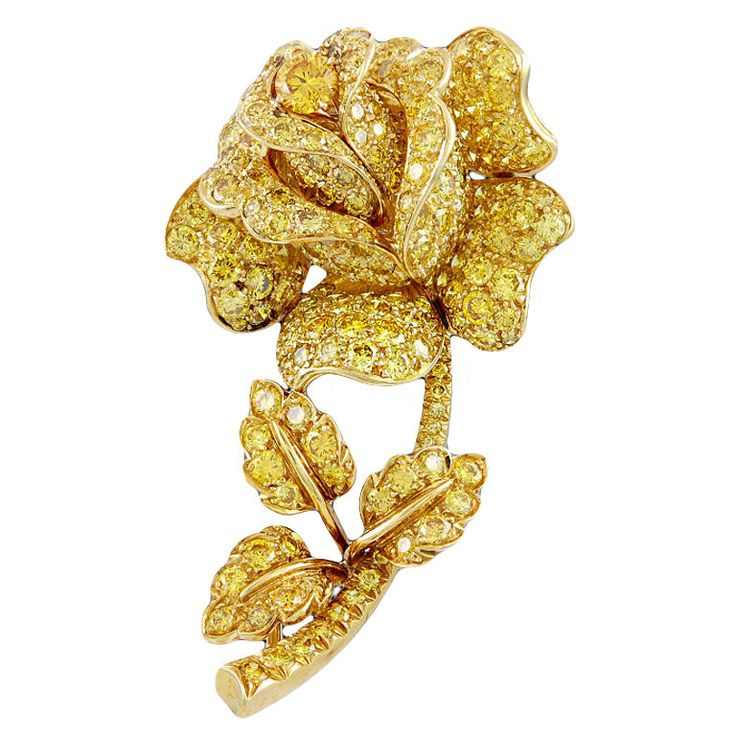 A magnificent Van Cleef & Arpels rose pin of gold set with very fine canary yellow diamonds throughout with a center intense yellow canary diamond in the bud.