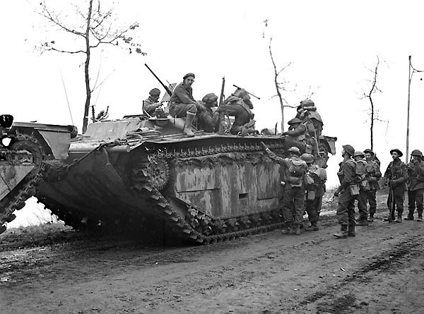 Infantrymen of the North Shore Regiment climbing onto an Alligator amphibious tracked vehicle during Operation VERITABLE near Nijmegen, Netherlands, 8 February 1945.