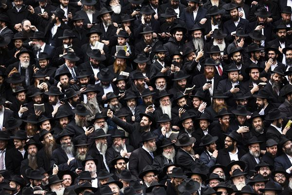 Hasidic Rabbis prepare for a group photo, part of the annual International Conference of Chabad-Lubavitch Emissaries, in front of Chabad Lubavitch World Headquarters in the Crown Heights neighborhood of Brooklyn, New York, on November 19, 2017 (Amir Levy/Getty -   Atlantic)