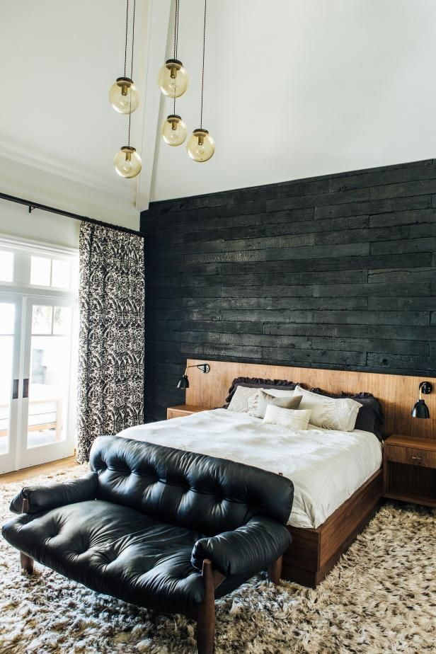 This transitional master retreat from FLO Design Studio features a striking charred accent wall behind the bed, along with a midcentury modern bed, a wood-patterned in the bathroom, and a lovely outdoor seating area.