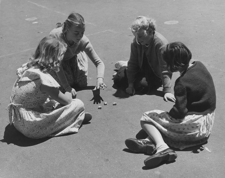 Four young girls sitting in a circle on an asphalt surface, playing Jacks with sheep knucklebones in a government school playground in Melbourne, Victoria, 1954.