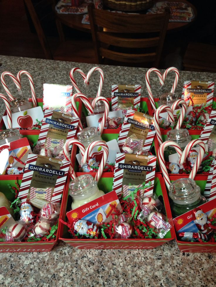 Christmas baskets for staff. Small Yankee candles with a gift card hot glued on candy canes hot glued together to make a heart and some fun  Christmas treats hidden inside. Small treat trays were bought in a three pack and red and green confetti was place