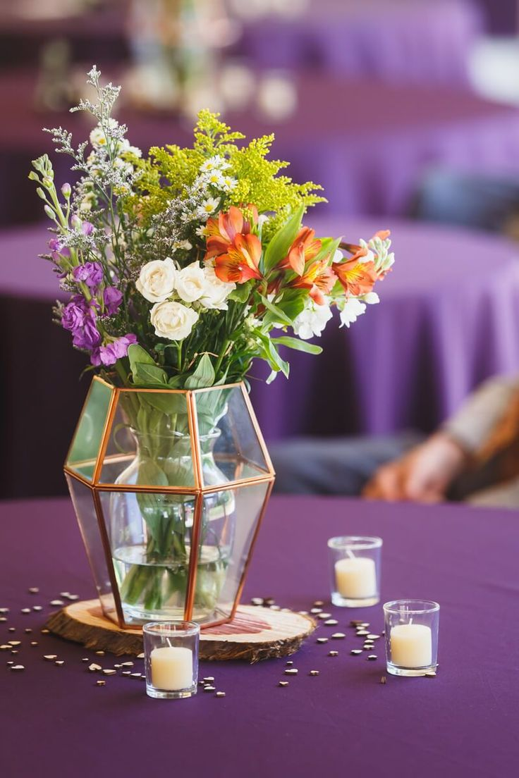 Simple Floral centerpiece in geometric vase and purple table cloth