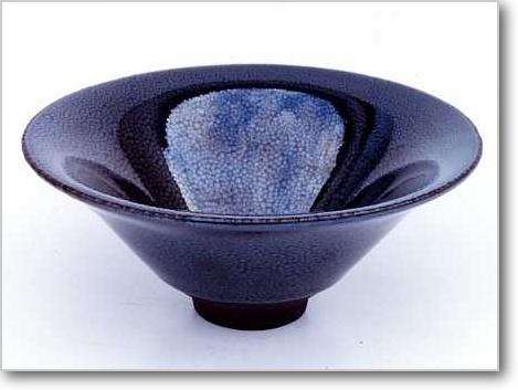 油滴広口天目茶碗   建窯  [宋時代]   A.D.12~13世紀  口径 19cm、高 6.5cm  Sung Dynasty.  12th-13th century. A.D.  Bowl with everted side, with oil-spotted black glaze,  named Yuteki Temmoku in Japan.  Chien ware.  M.D.19cm、H.6.5cm  日本でしか見られない虹様の出る耀変天目も何時かはこの手の中にと思っていますが今のところ見たことがありませんので説明できません。    油滴天目はたくさん見ますが耀変は、まだあると確信めいたものはありますが残念ながら縁がありません。    しかし我々の常識を越えたような窯変はまだまだあり、何が出てくるか分かりません。    それが中国の中国たらんところであると思っています。