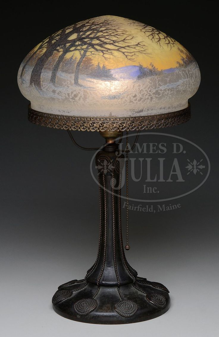 """HANDEL TEROMA WINTER SCENE LAMP. Handel table lamp has Teroma mushroom shade with enameled winter scene of barren trees rising from snow covered ground against mottled orange shading to yellow sky. Signed on inside rim """"Hande_ _970"""". Shade rests on original Handel Moorish base with round platform foot and Moorish metal rope decoration rising up the stem which supports a single socket and three arm spider attaching cast openwork shade ring. Base has rich brown patina. Signed on underside in…"""