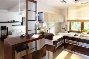Między kuchnią a pokojem z katem jadalnym stoi barek (fornirowany limbą) z wysokimi stołkami. Drzwi przypominają japoński parawan, tylko papier został zastąpiony mlecznym szkłem. - zdjęcie