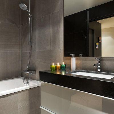 La salle de bains la plus spacieuse est accessible de la chambre du fils et sert aussi à sa mère. Les murs sont revêtus d'un carrelage de grès cérame imitant la pierre. Le meuble sous vasque (Ikea) est recouvert d'un plan en granit adossé à une crédence en faux-cuir.