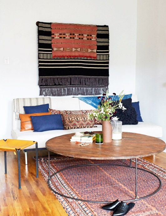 eclectic throw pillows on white sofa with wall hanging. / sfgirlbybay