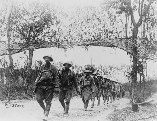 American soldiers marching along a road northwest of Verdun, France, November 5, 1918. By the U.S. Army Signal Corps.