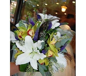Hand tied bouquet of green cymbidium orchids, white hybrid lilies, purple veronica, seeded euc, ostrich feathers, and peacock feathers.