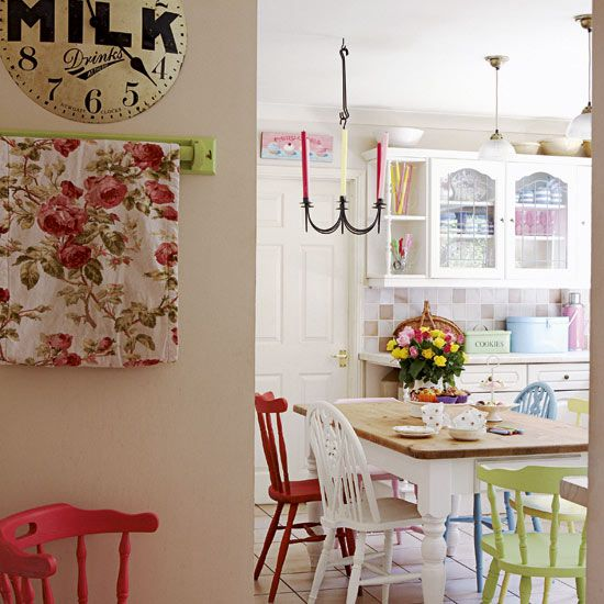 Bright and colourful country kitchen - mismatched vintage chairs, milk clock by Newgate Clocks, floral prints, candelabra, flowers and wooden kitchen table