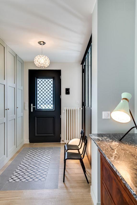 Une entrée avec un sol parquet et carreaux de ciment en forme de tapis