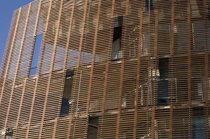 Parc de Recerca Biomèdica de Barcelona (PRBB) / PINEARQ (8)  El revestimiento de la fachada está constituido por una piel de bri-soleil de madera de cedro rojo que nunca toca el suelo: de esta forma se consigue sacar peso a un edificio que, por su concepción compacta y unitaria, presenta una grandeza considerable.
