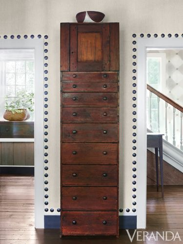 Designed by the 20th-century Atlanta architect James Means, it's a 1960s take on a Colonial-era farmhouse, but it's also a sophisticated fusion of reclaimed materials, singular furnishings, and some lighthearted touches. Oversize nailheads echo drawer pulls. Walls in Rogers & Goffigon linen. Nailhead trim, Samuel & Sons.   - Veranda.com