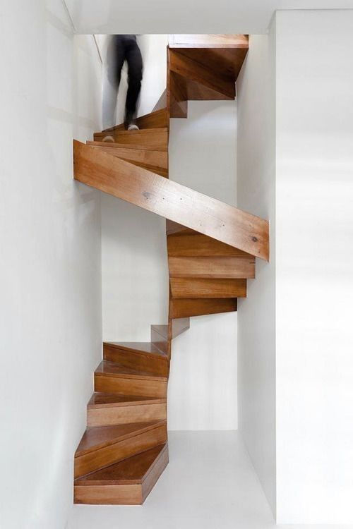 A modern wooden staircase in a renovation of a historical apartment by Porto, Portugal, firm Ezzo.