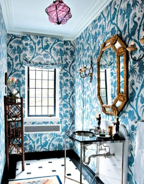 Bold blue and white floral print wallpaper in a petite powder room with gold octagon paneled mirror and console sink.