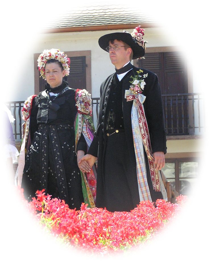The traditional wedding costume in Hunspach in the North of Alsace (France) - Two bouquets with lots of colourful ribbons were fixed on each sleeve of the bridal dress. The men also wore a small bouquet in their buttonholes.