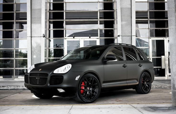 "Customized Porsche Cayenne Turbo S with full matte black exterior wrap, smoked lights, painted black exterior trim, lowered on 22"" lmola wheels."