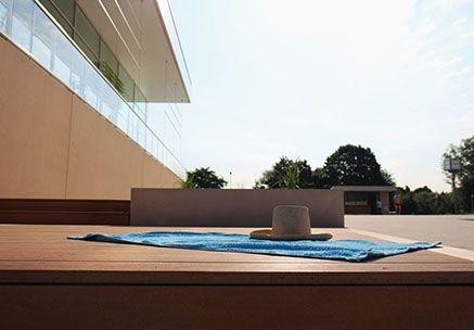 WPC Barfußdielen auf einer Terrasse eines Freibads mit Handtuch und Hut