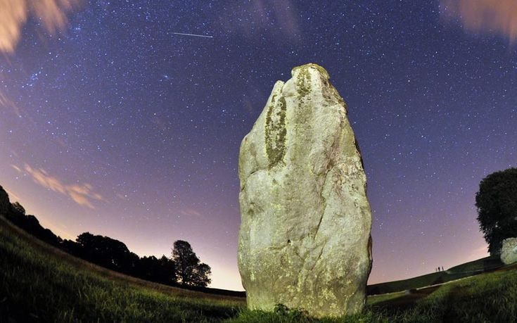 A meteor is seen during the Perseids meteor shower over the one of the stones of the Avebury's Neolithic henge monument in Wiltshire
