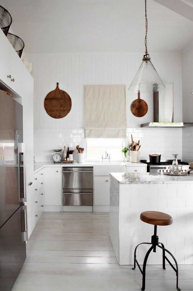 Kitchen Vintage European timber chopping boards and mango wood stools from Orson & Blake add warmth to the all-white kitchen