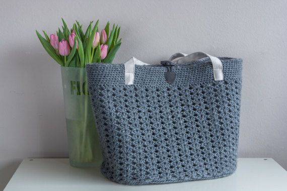 A nice big gray crochet bag. The lining is 3 mm thick felt so the bag stays pretty upright without anything in it. The bag closes with a wood / string closure and the handle is of suedine.  The size is 40 x 27 x 33 (l x w xnh).