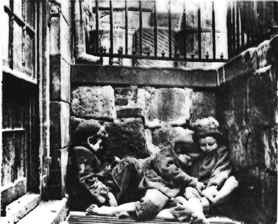 London Poor: 19th Century London street children huddle together for warmth and safety.