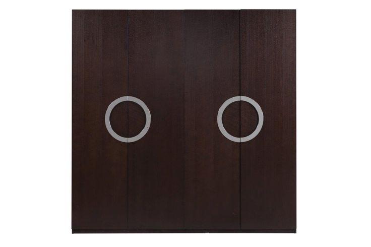 Этот шкаф – вместительная и функциональная деталь интерьера, Этот шкаф отлично впишется в современный интерьер, его можно поставить в спальне или в холле. Шкаф выполнен в шоколадном цвете, а ручки сделаны в оригинальной манере, они образуют два круга посередине дверей шкафа, когда находятся в закрытом положении. Внутри шкафа найдется место для одежды, обуви и аксессуаров. В дополнение к шкафу можно также приобрести тумбу, туалетный столик и другие предметы интерьера из этой же коллекции…